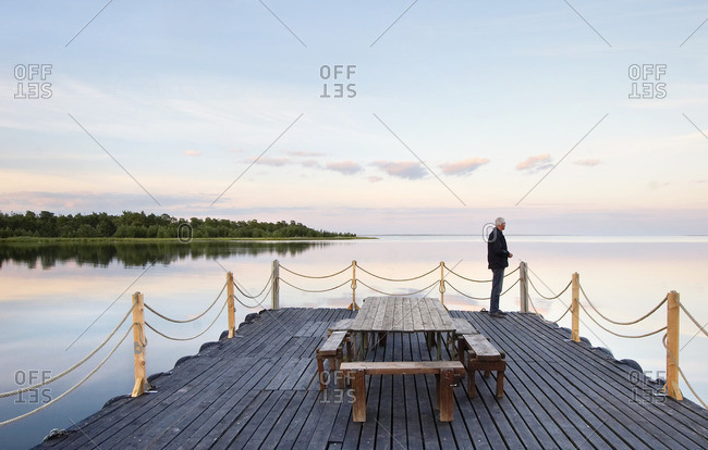 Sweden, Gotland, Lergrav, Man standing on wooden deck and looking at sea