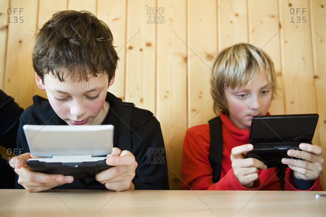 Two boys playing handheld game