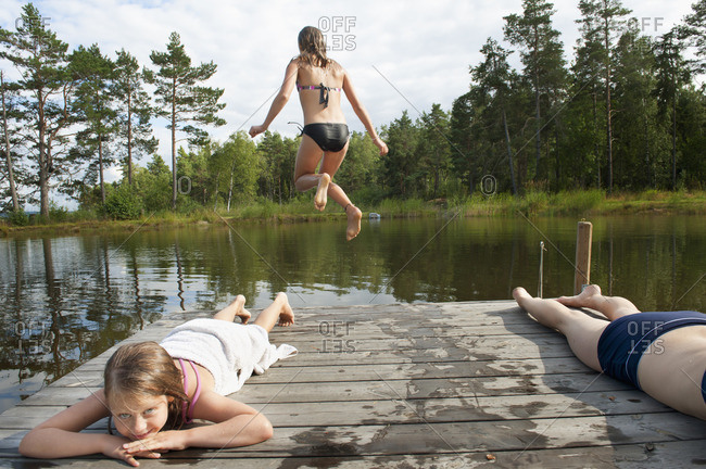 Sweden, Vastra Gotaland, Kallandso, Girls (8-9, 12-13, 16-17)) resting near lake