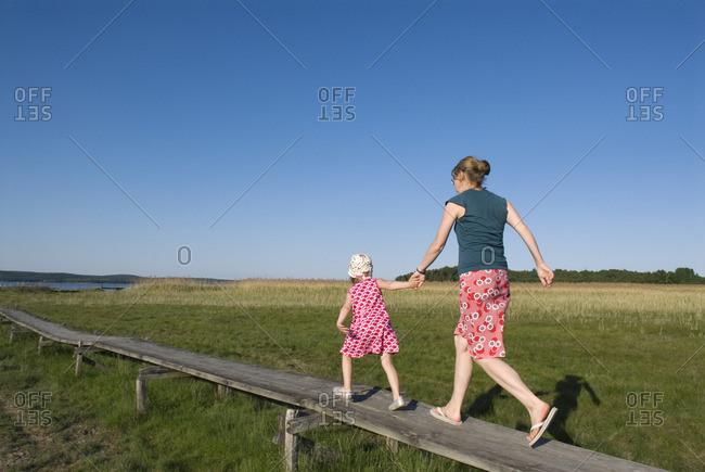 Sweden, Ostergotland, Woman running with her daughter along wooden footbridge