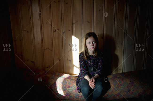 Girl sitting against wooden wall