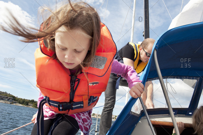 Sweden, Bohuslan, Girl sailing with her father