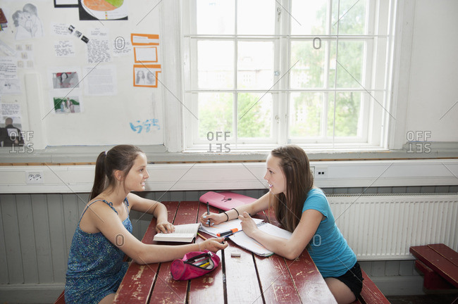 Two girls (14-15) sitting at table, studying
