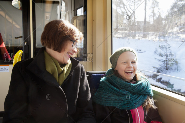Sweden, Stockholm, Girl sitting with grandmother in tram and laughing