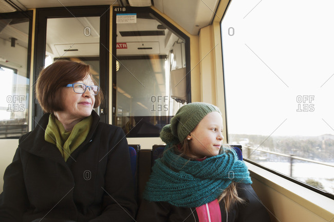 Sweden, Stockholm, Girl sitting with grandmother in tram and looking through window