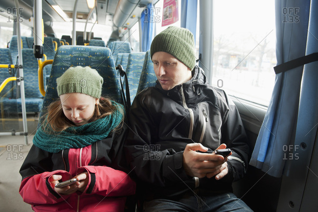 Sweden, Stockholm, Girl with father sitting in tram and using smart phones