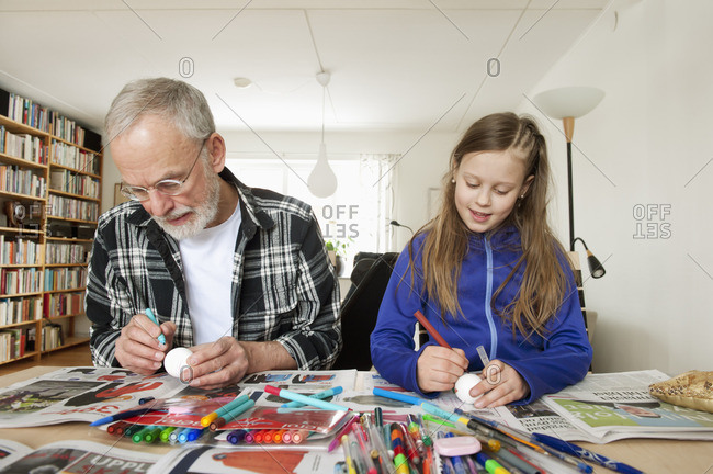 Sweden, Girl with grandfather coloring eggs in living room