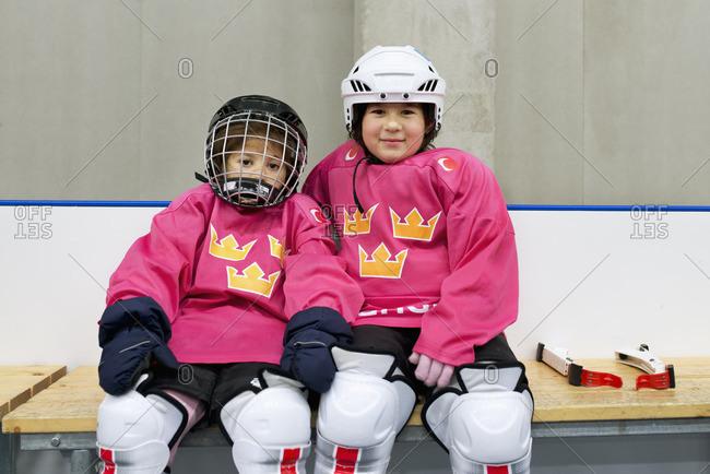 Sweden, Girls in ice hockey uniform sitting on bench