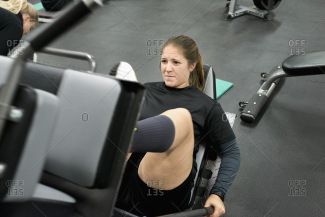 Sweden, Young woman exercising on leg press machine