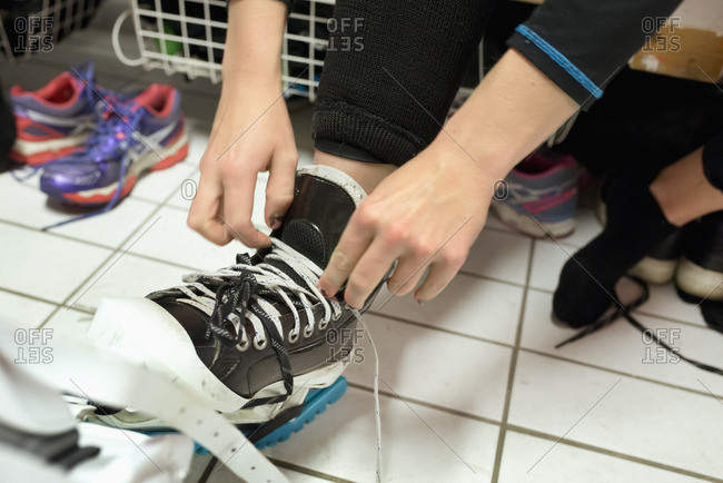 Sweden, Young woman tying shoelaces in locker room