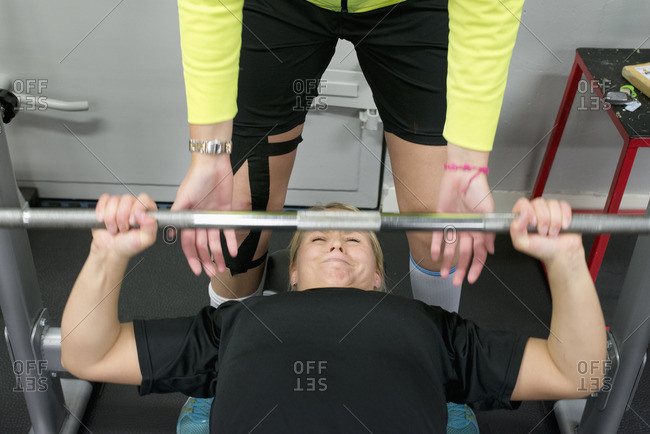 Sweden, Young woman weight lifting with barbell in gym