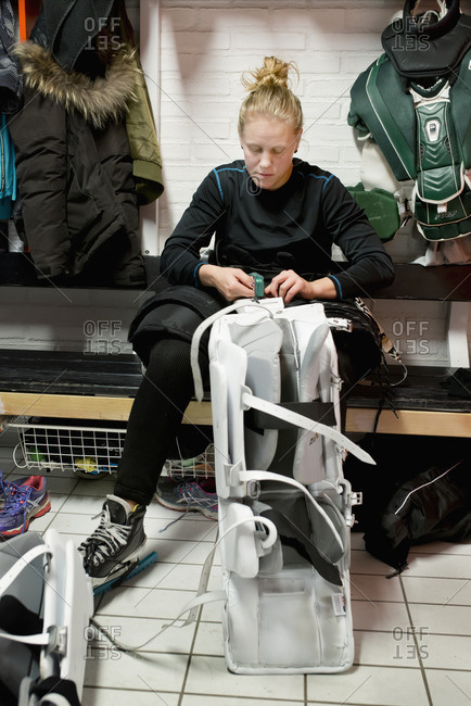 Sweden, Young ice hockey player sitting with bag on bench in locker room