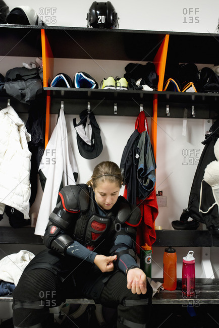 Sweden, Young ice hockey player sitting on bench and getting ready in locker room