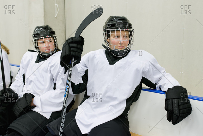 Sweden, Young ice hockey players sitting on bench waiting for game