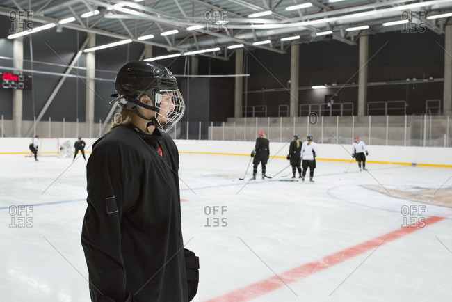 Sweden, Young hockey player wearing helmet standing on rink