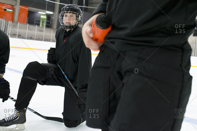 Sweden, Young hockey player wearing helmet kneeling on rink