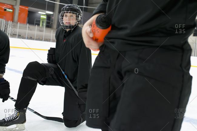 Sweden, Young hockey player wearing helmet kneeling on rink