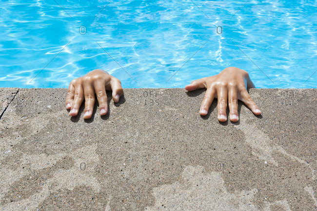 Sweden, Ostergotland, Hands on edge of swimming pool