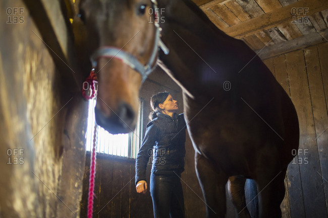 Sweden, Ostergotland, Vaderstad, Woman in stables