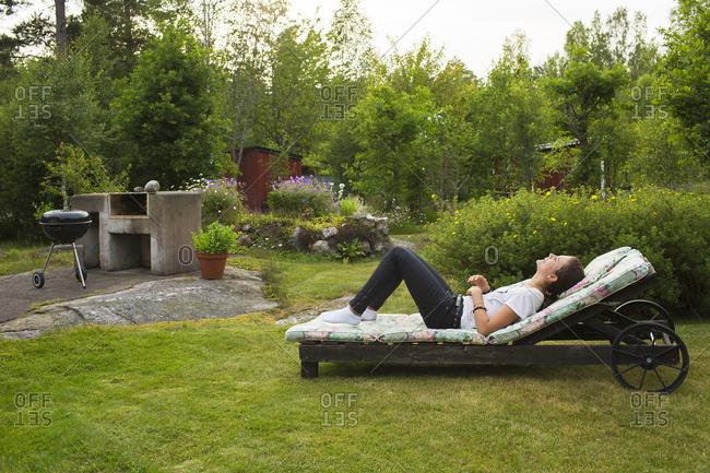 Sweden, Ostergotland, Girl relaxing in garden