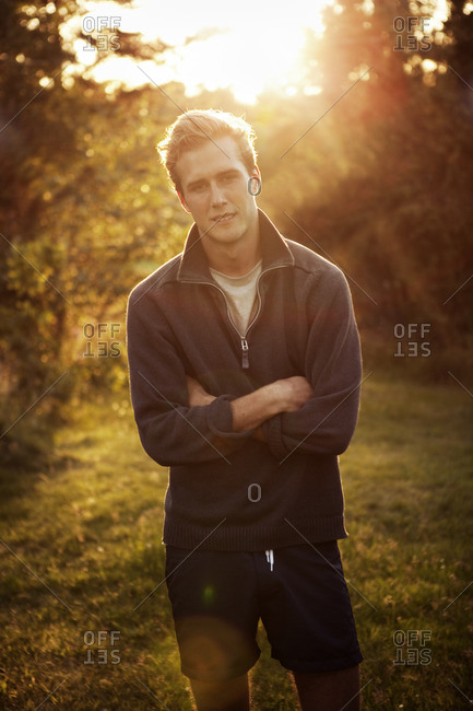 Sweden, Smaland, Loftahammar, Portrait of man standing with arms crossed at sunset