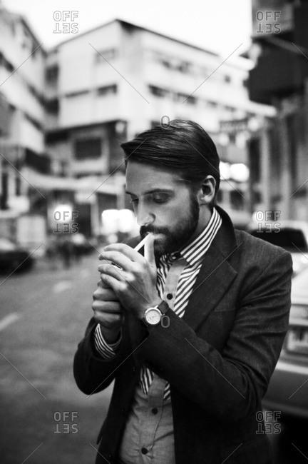 Thailand, Bangkok, Man standing in street and lighting cigarette