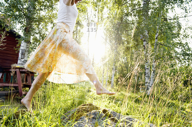 Sweden, Dalarna, Svardsjo, Young woman jumping in grass in backyard