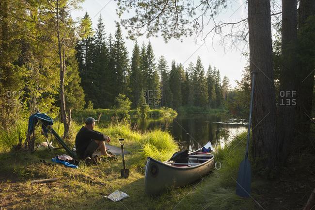Sweden, Vastmanland, Svartalven, Man sitting by canoe on riverbank
