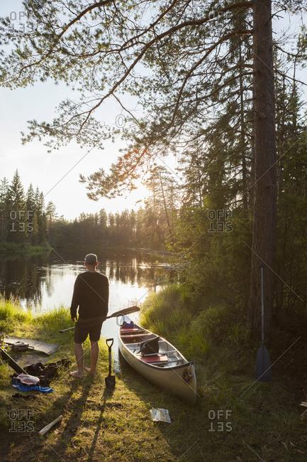 Sweden, Vastmanland, Svartalven, Man by canoe on riverbank