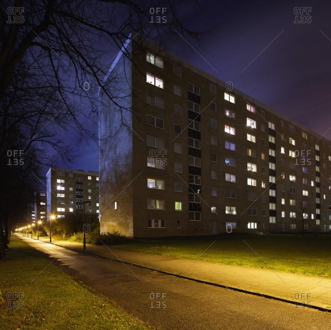 Sweden, Skane, Malmo, Rosengard, Illuminated buildings along road at night