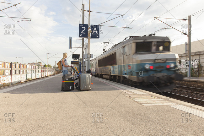 France, Nice, Woman with baby on railroad station platform