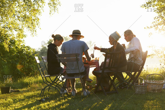 Sweden, Sodermanland, Jarna, Family having dinner in backyard at sunset