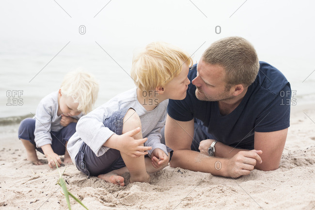 Sweden, Gotland, Ljugarn, Two boys spending time with man on beach