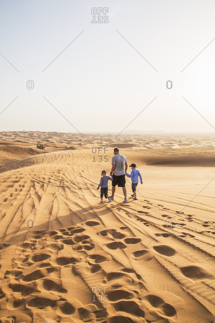 United Arab Emirates, Dubai, Father with sons walking in desert