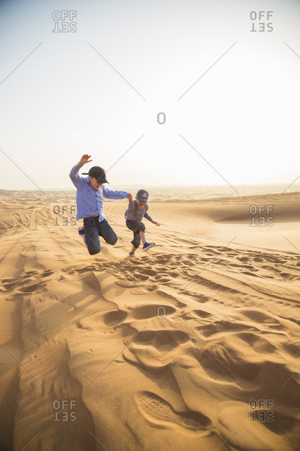 United Arab Emirates, Dubai, Two boys jumping on sand in desert