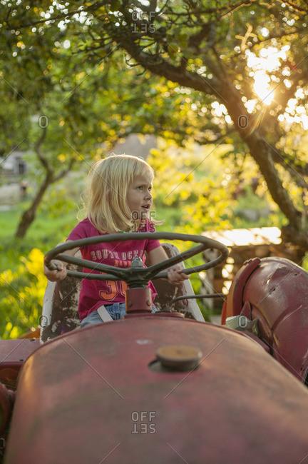 Sweden, Skane, Osterlen, Girl on tractor