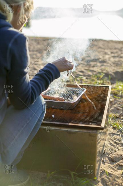 Sweden, Vastergotland, Lerum, Woman cooking by lake