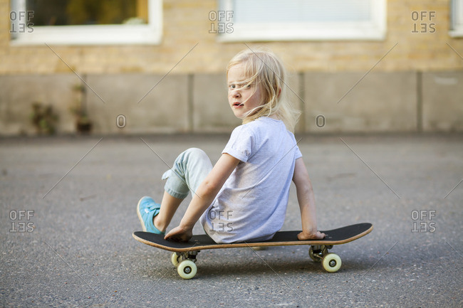 Sweden, Vastergotland, Lerum, Girl sitting on skateboard