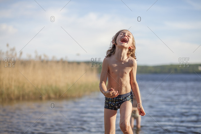 Sweden, Vastergotland, Lerum, Lake Aspen, Boy standing in lake