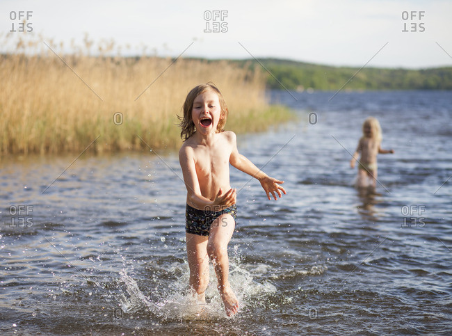 Sweden, Vastergotland, Lerum, Lake Aspen, Boy and girl playing in lake