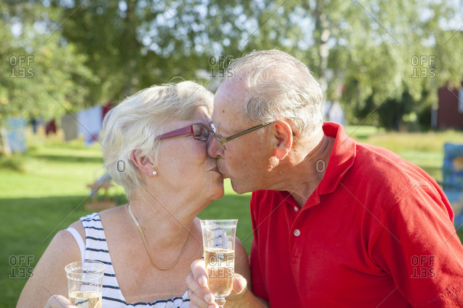 Sweden, Senior couple toasting with champagne flute and kissing