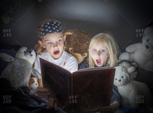 Sweden, Vastergotland, Lerum, Siblings reading book in bed
