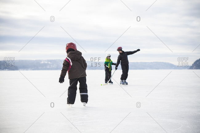 Sweden, Vastergotland, Lerum, Lake Aspen, Mom playing ice hockey with her two children on lake