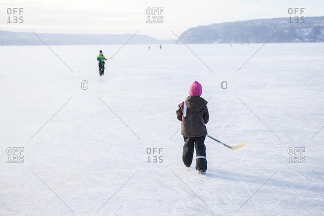 Sweden, Vastergotland, Lerum, Lake Aspen, Siblings playing ice hockey on lake