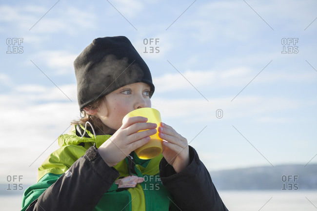 Sweden, Vastergotland, Lerum, Lake Aspen, Boy drinking tea outdoors