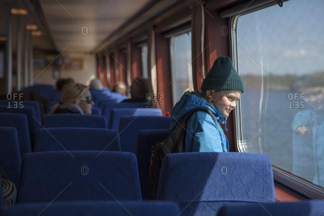 Sweden, Gothenburg Archipelago, Vastergotland, Styrso, Boy looking through train window