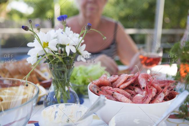 Sweden, Vastergotland, Lerum, Bowl of shrimps and flower vase on table, woman sitting in background
