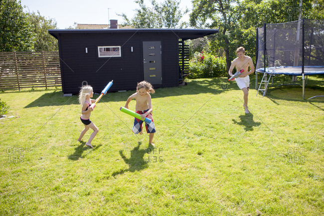 Sweden, Vastergotland, Lerum, Siblings playing with water guns in backyard