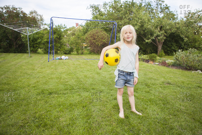 Sweden, Vastergotland, Lerum, Portrait of girl with soccer ball standing in backyard