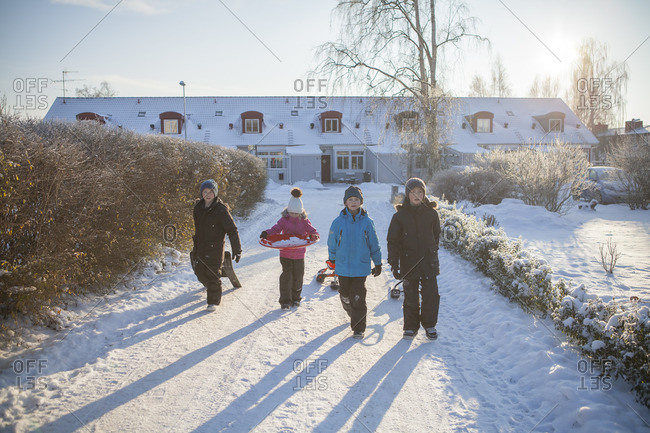 Sweden, Vastergotland, Lerum, Portrait of three boys and girl walking along snowy driveway, dragging sleds